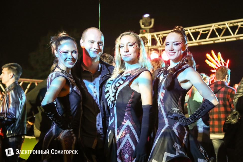 Три девочки в красных костюмах и организатор фестиваля
