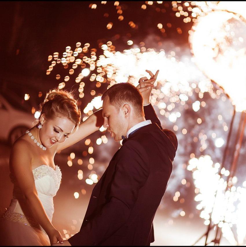Жених и невеста танцуют на улице, вокруг них пиро фонтаны
