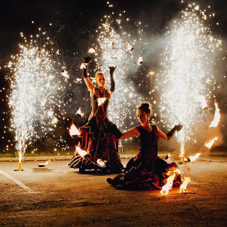 Две артистки огненного шоу на фоне серебристых фонтанов крутят веера