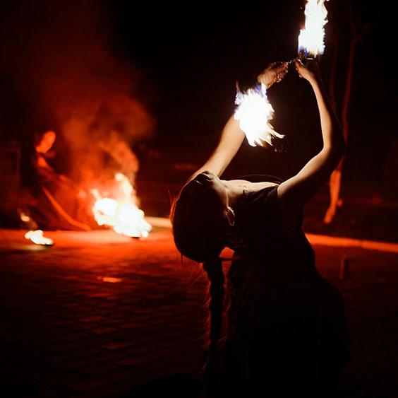 фаерщица крутит огненные пои в красивом прогибе