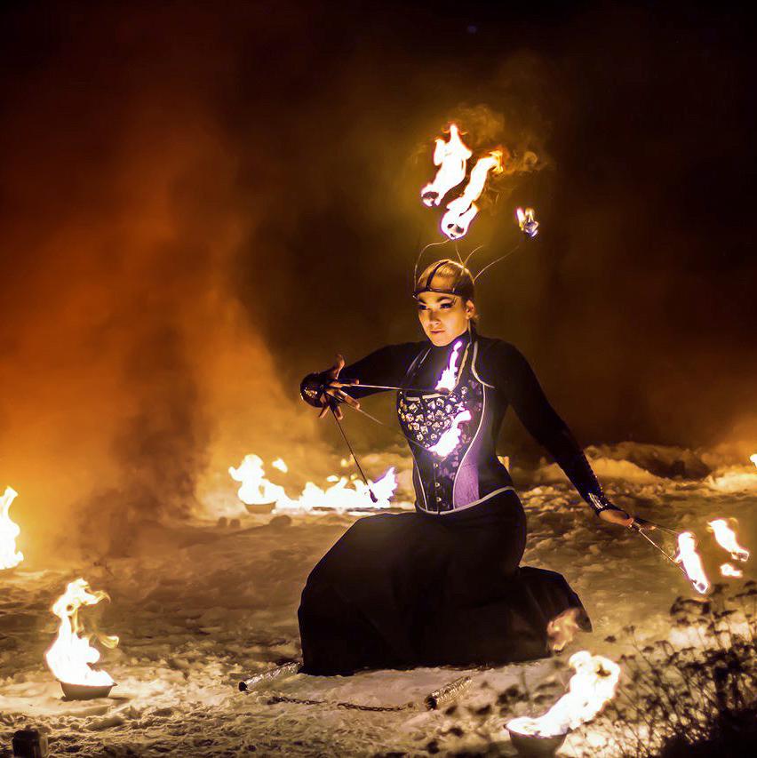 Артистка огненного шоу выступает в огненной короне