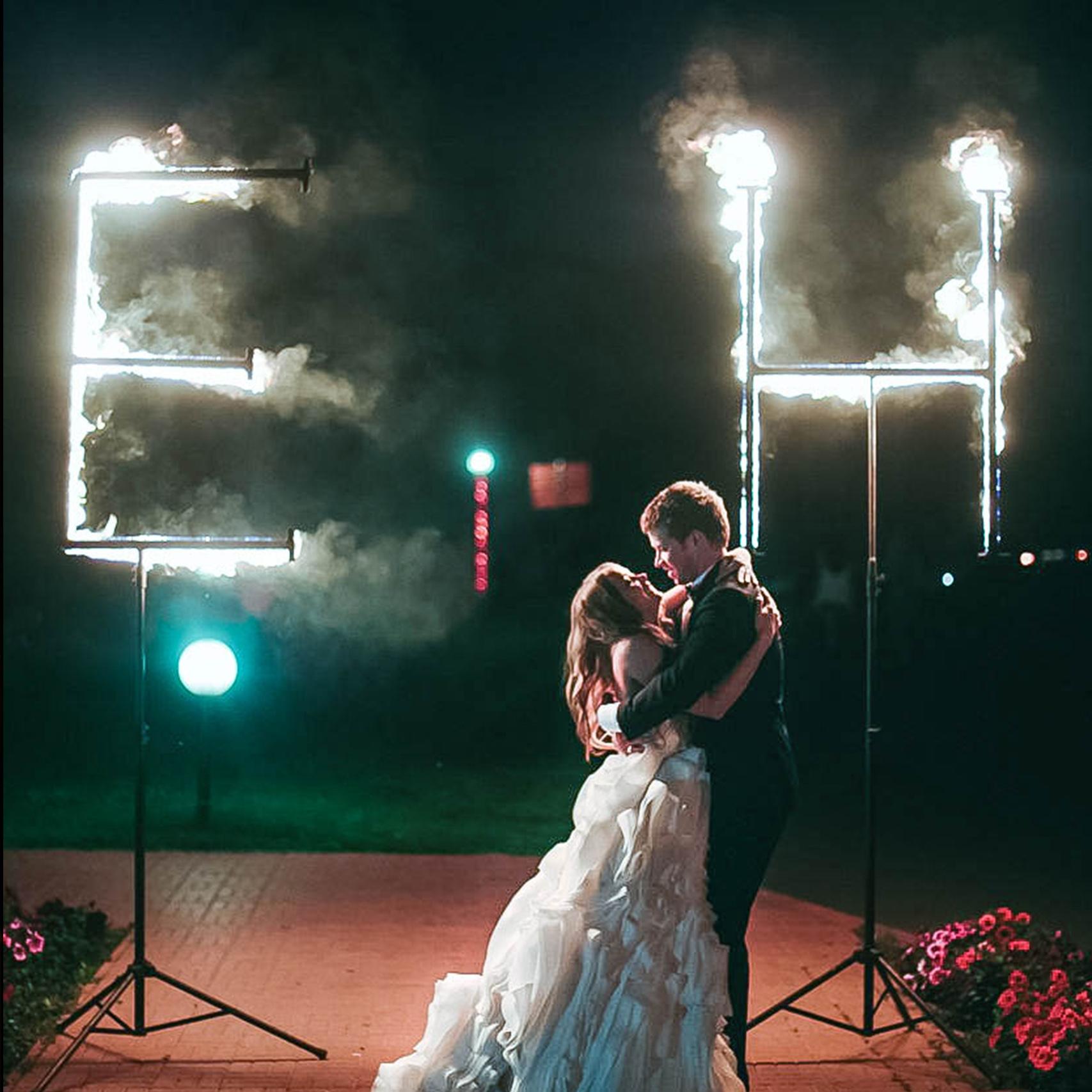 свадебная пара обнимается на фоне огромных огненных букв