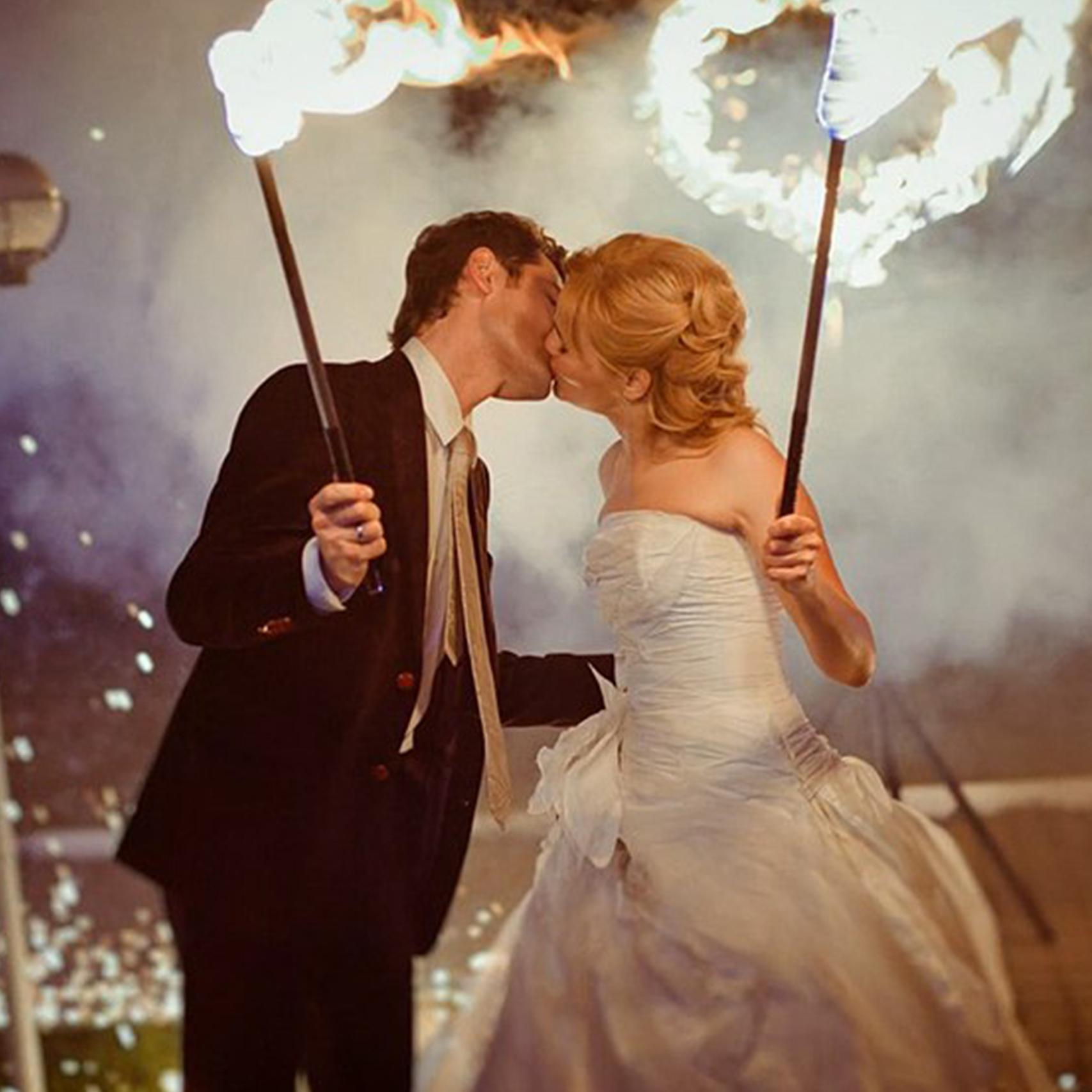 Жених и невеста крупным планом с огненными факелами целуют друг друга
