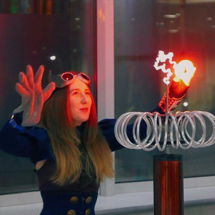 Артистка в стим-панк костюме показывает шоу с молниями
