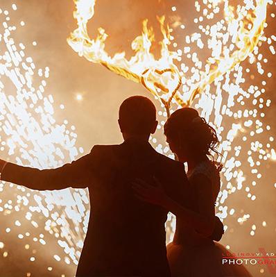Силуэты жениха и невесты на фоне искр и огненных сердец