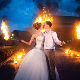 Поцелуй пары на фоне огня с факелами в руках