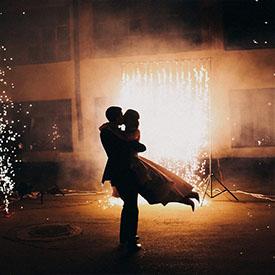 Силуэт пары, парень кружит девушку в красивом платье на фоне искр