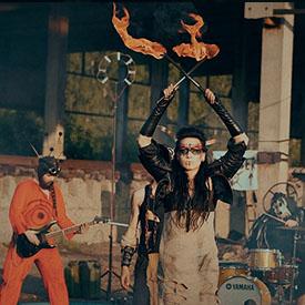 Девушка из шоу TANDAVA с факелами в костюме МэдМакс