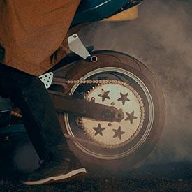 Колесо мотоцикла в движении и пыли