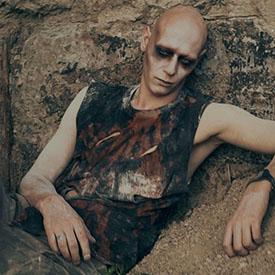 Лежащий на камнях персонаж из фаер-шоу MadMax
