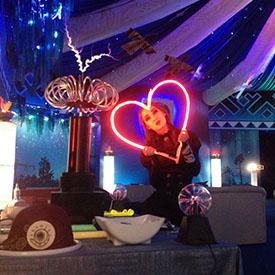 Артистка Тандава шоу позирует с красным сердцем и катушкой Тесла