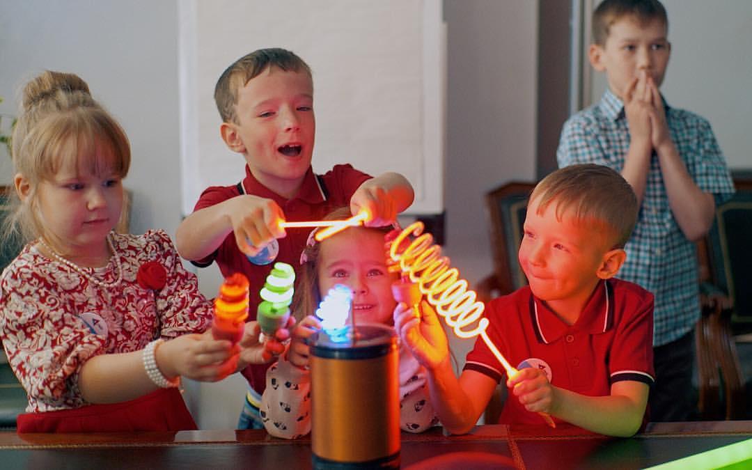 Дети зажигают лампочки у маленькой катушки тесла