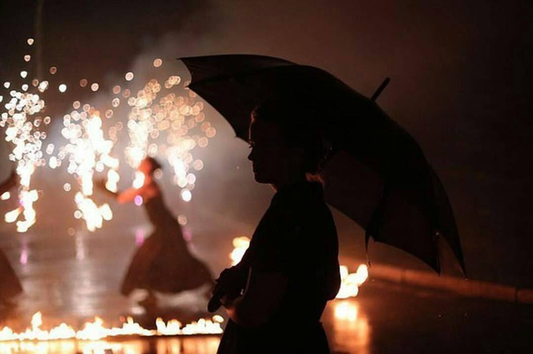 Огненное шоу (фаер-шоу) в Екатеринбурге в дождь, гостья смотрит шоу с зонтом